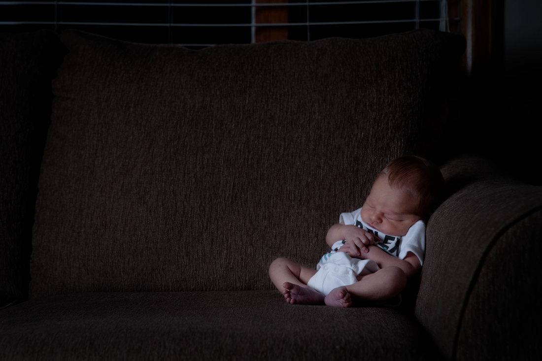 Newborn Photography. baby sitting on couch