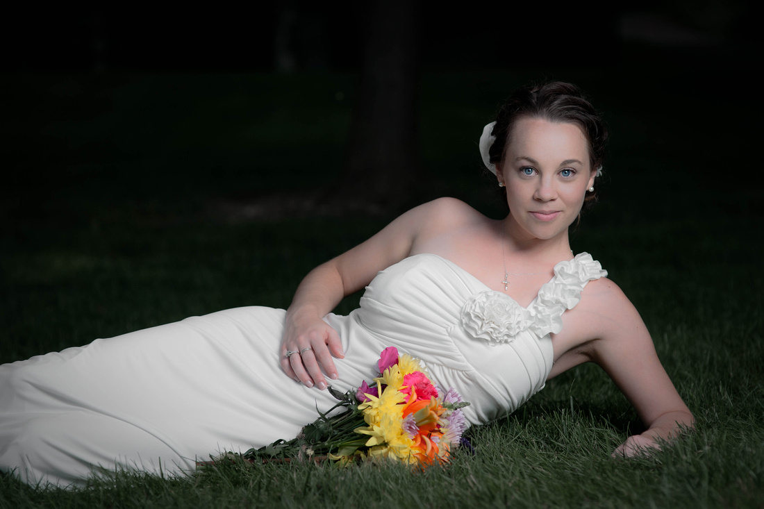 Bride laying in grass with flowers in front of her. Johnstown PA wedding photography.