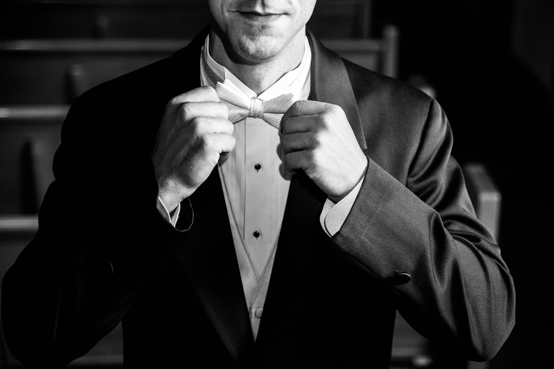 Groom adjusting tie and bow tie. Johnstown PA wedding photographer.