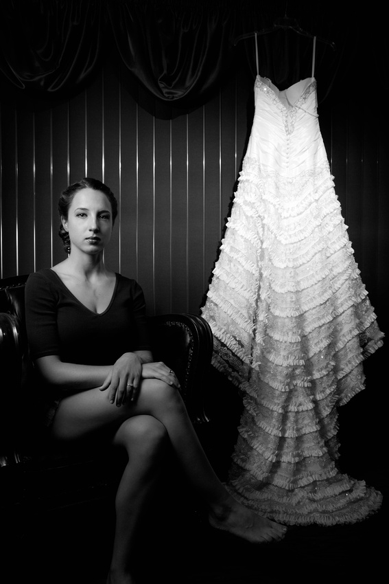 Bride sitting on chair next to wedding gown. Johnstown PA wedding photographer