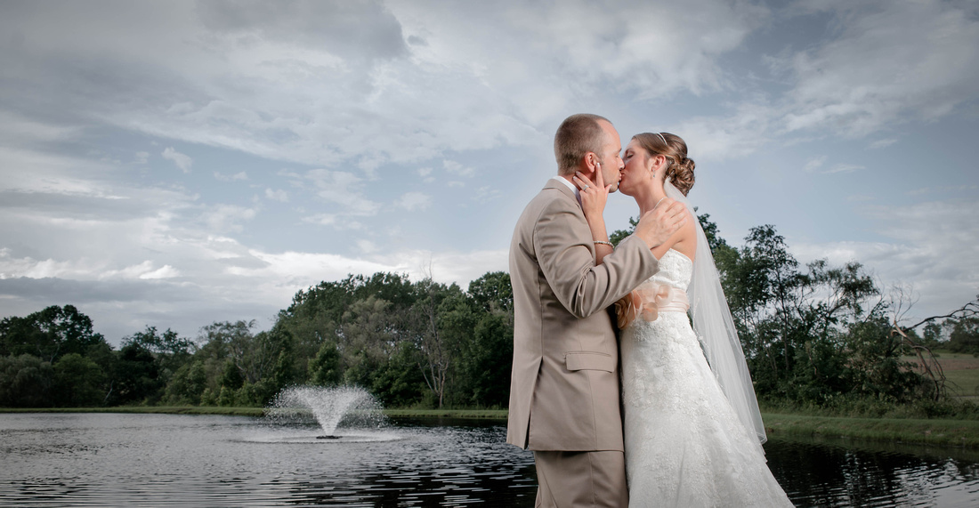 Bride kissing groom in front of pond with fountain. Somerset  PA wedding photography.
