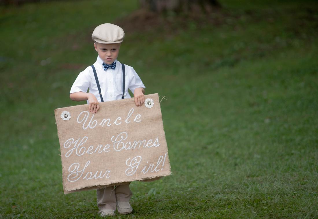 Ring bearer walking down isle holding sign. Somerset PA wedding photography.