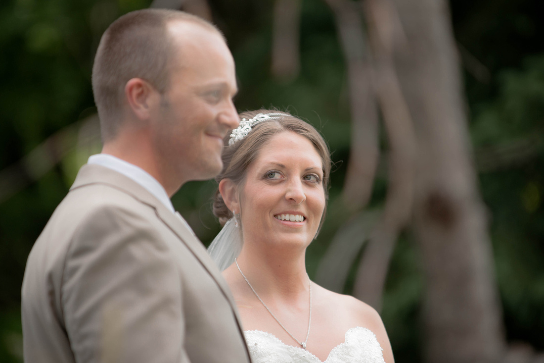 Bride looking at groom and smiling as she stands beside him at alter. Somerset PA wedding photography.