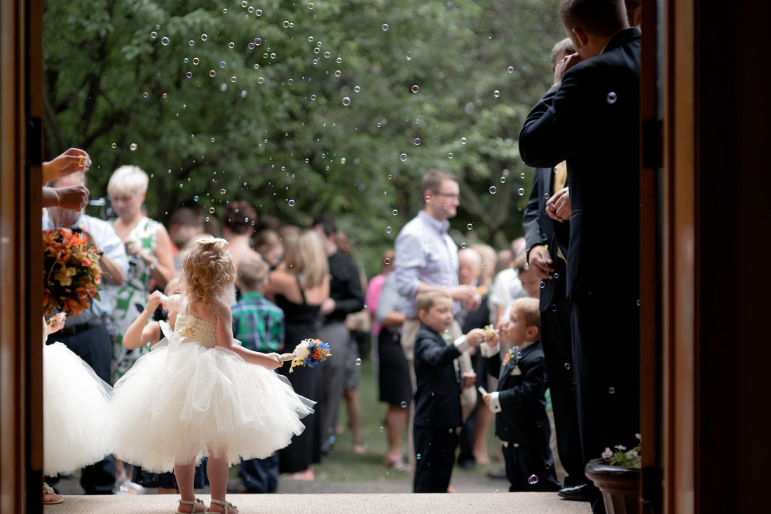 Flower girl with bubbles around her after wedding. Johnstown PA wedding photographer.