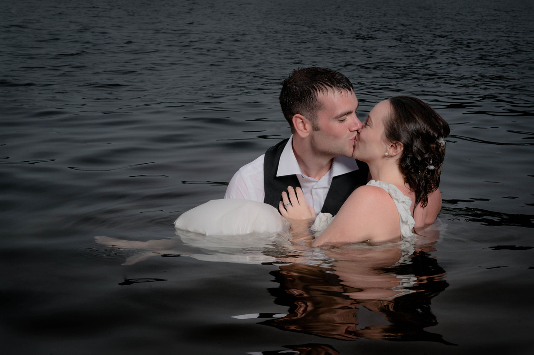 Bride and groom kissing in water after taking the plunge. trash the dress. Johnstown PA wedding photography.