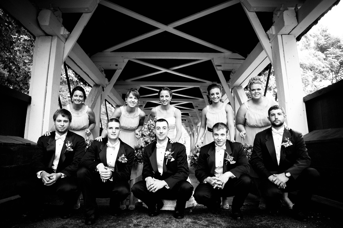 Bride, groom and wedding party in covered bridge. Johnstown Pa wedding photographer.