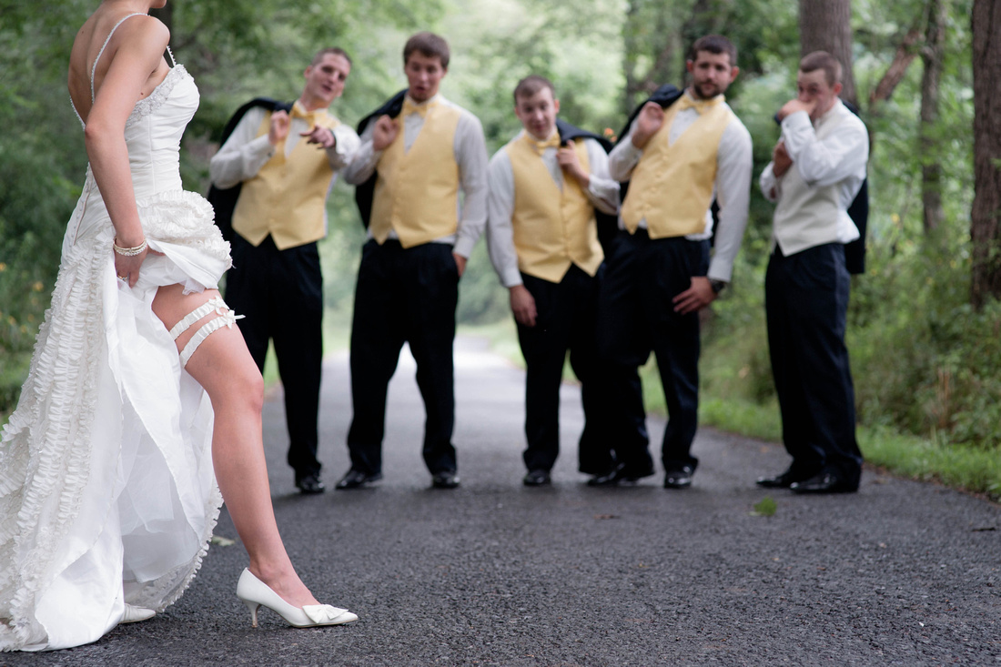 Funny wedding photo of bride showing garter and leg to grooms men. Johnstown PA wedding photographer.