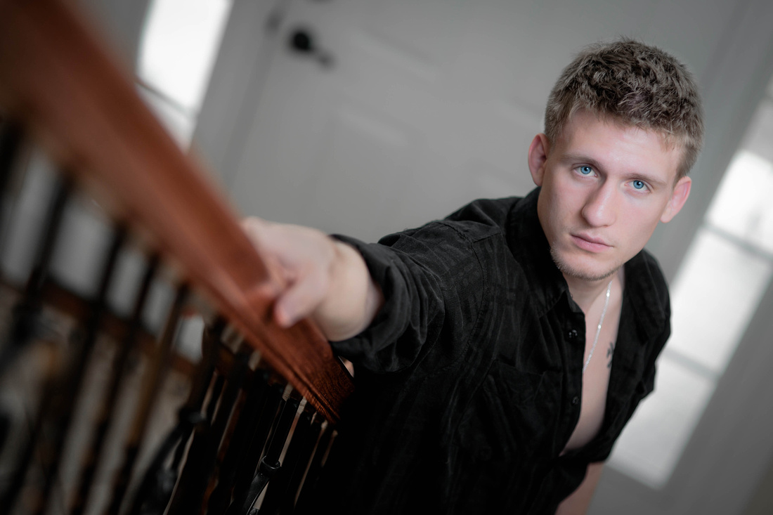 Senior portrait of man standing at bottom of stairs. Johnstown pa senior portrait photography.