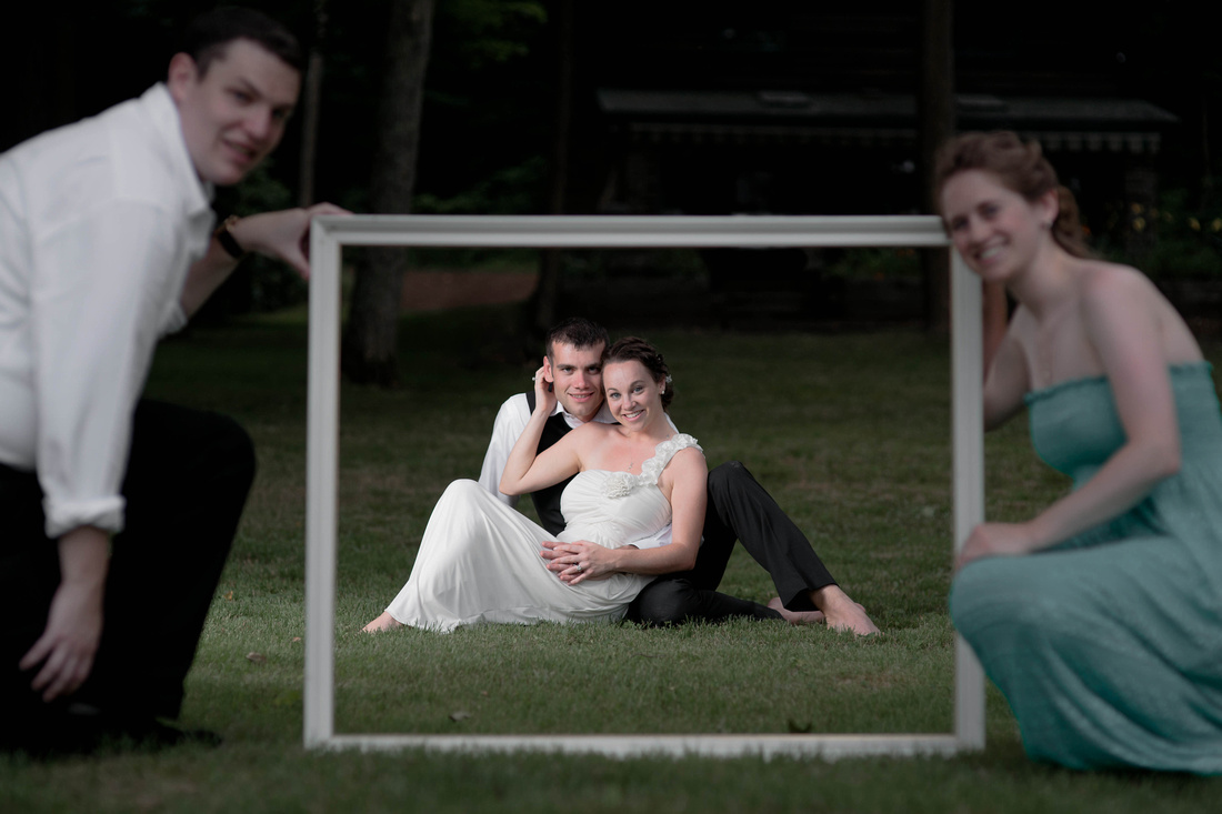 Portrait of bride and groom in a wooden frame. Best man, Maid of honor holding it. Johnstown PA wedding photography.