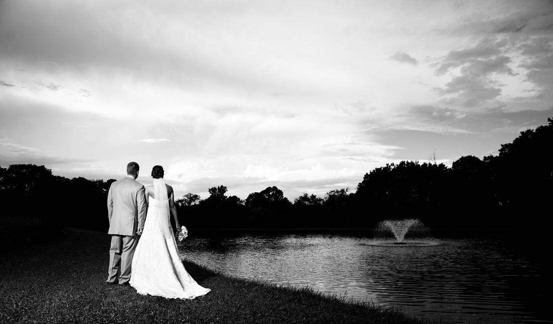 black and white portrait of bride and groom standing beside pond and fountain. Somerset PA wedding photography.