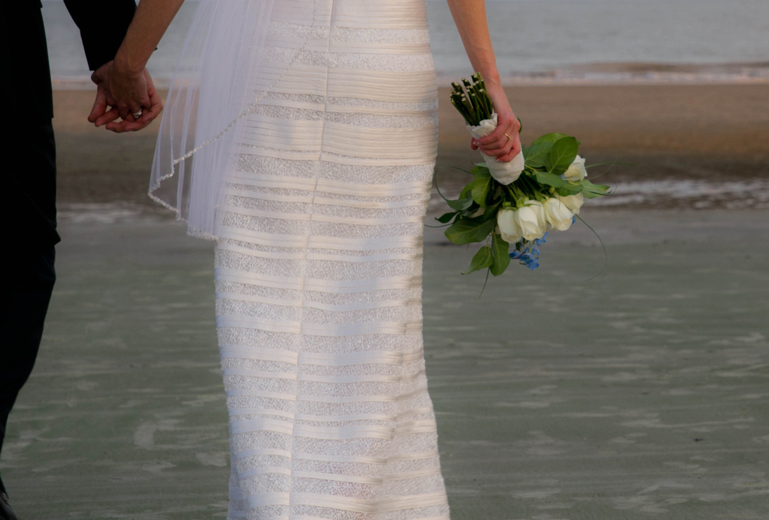 wedding picture of bride and groom holding hands by the ocean. bouquet.