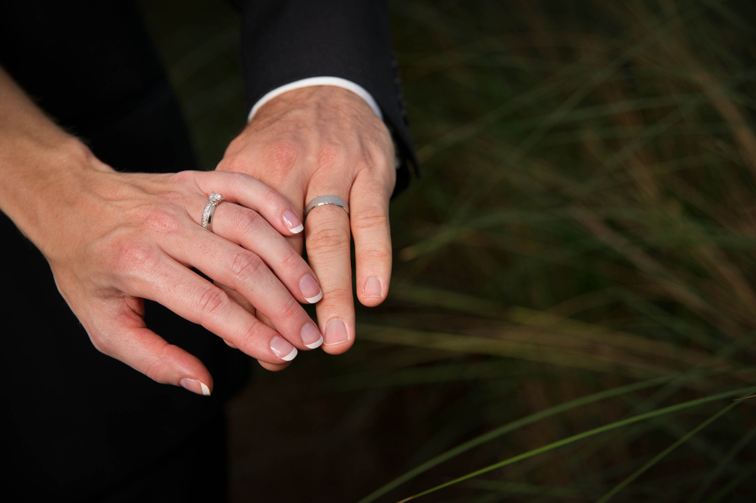 wedding picture of bride and groom showing their rings.