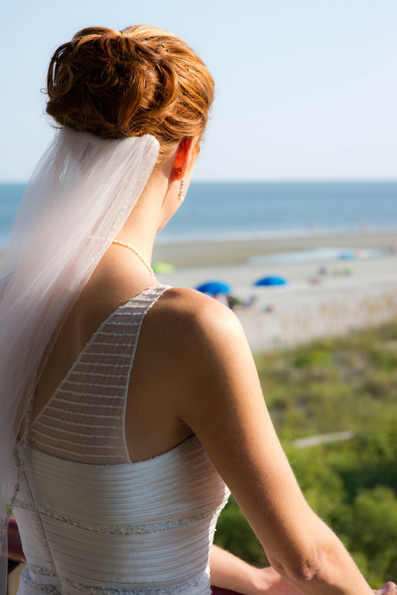 wedding picture of bride overlooking beach from balchony
