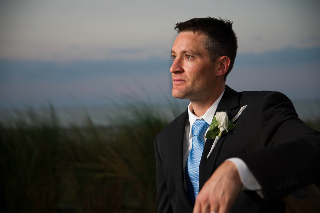 wedding picture of groom by the ocean.