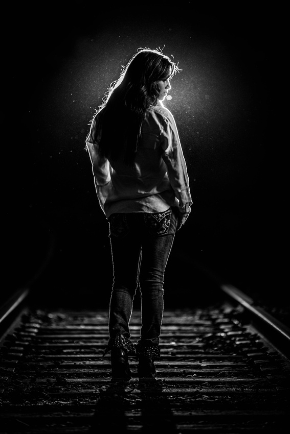Senior Portrait Photography. Young woman standing on railroad tracks
