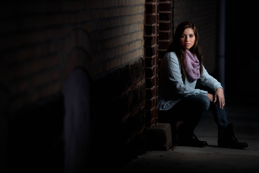 Senior Portrait Photography. young woman sitting on side walk.