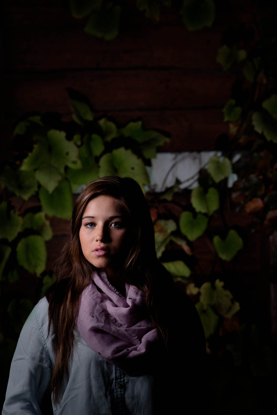 Senior Portrait Photography. young woman standing in front of building with ivy.