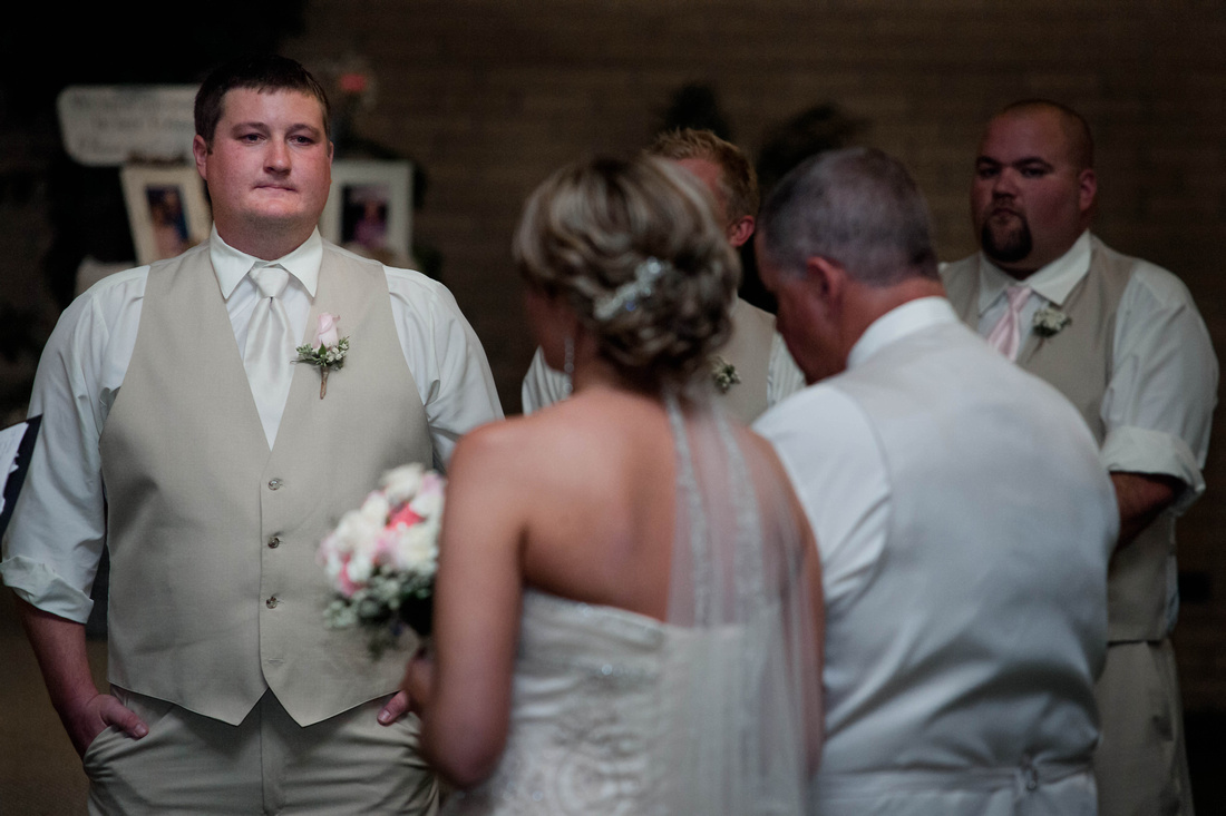 Wedding Photography. groom looking at bride as she comes down the isle.