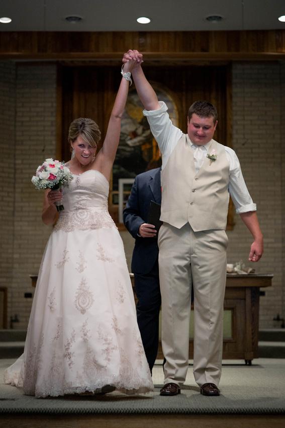 Wedding Photography. bride and groom raising hands