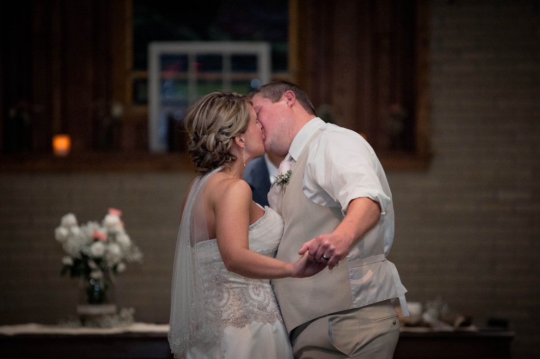 Wedding Photography. bride and groom kissing after being pronounced man and wife.