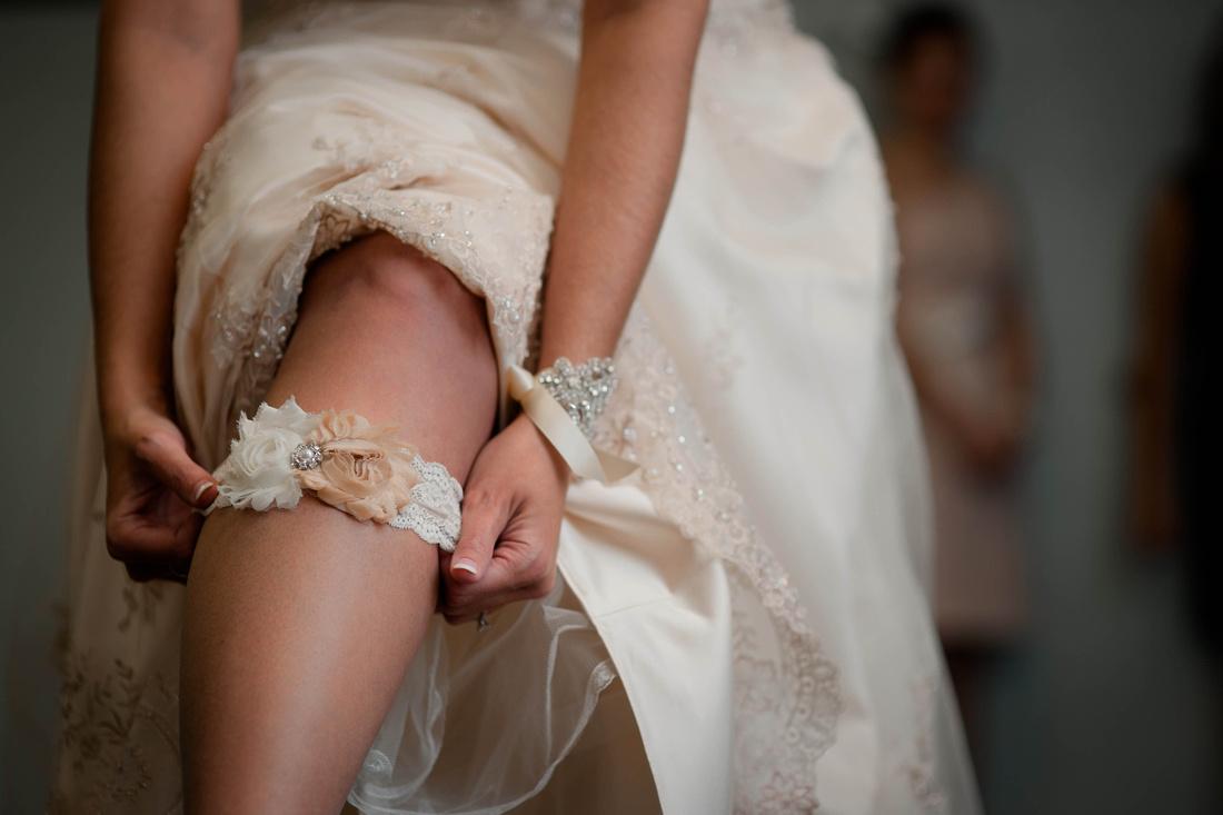 Wedding Photography. bride pulling on garter.