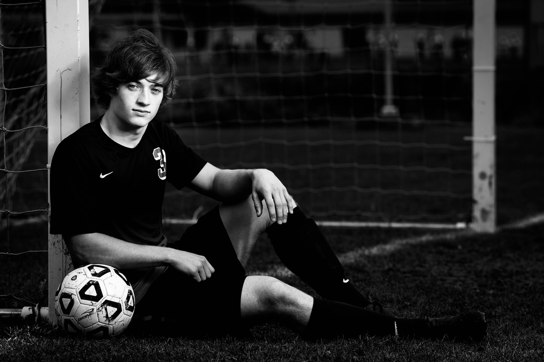 Senior Portrait Photography. senior sitting on ground leaning his elbow in soccer ball.