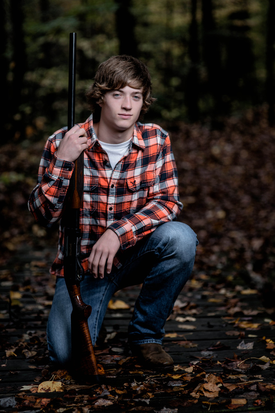 Senior Portrait Photography. senior kneeling down with rifle.