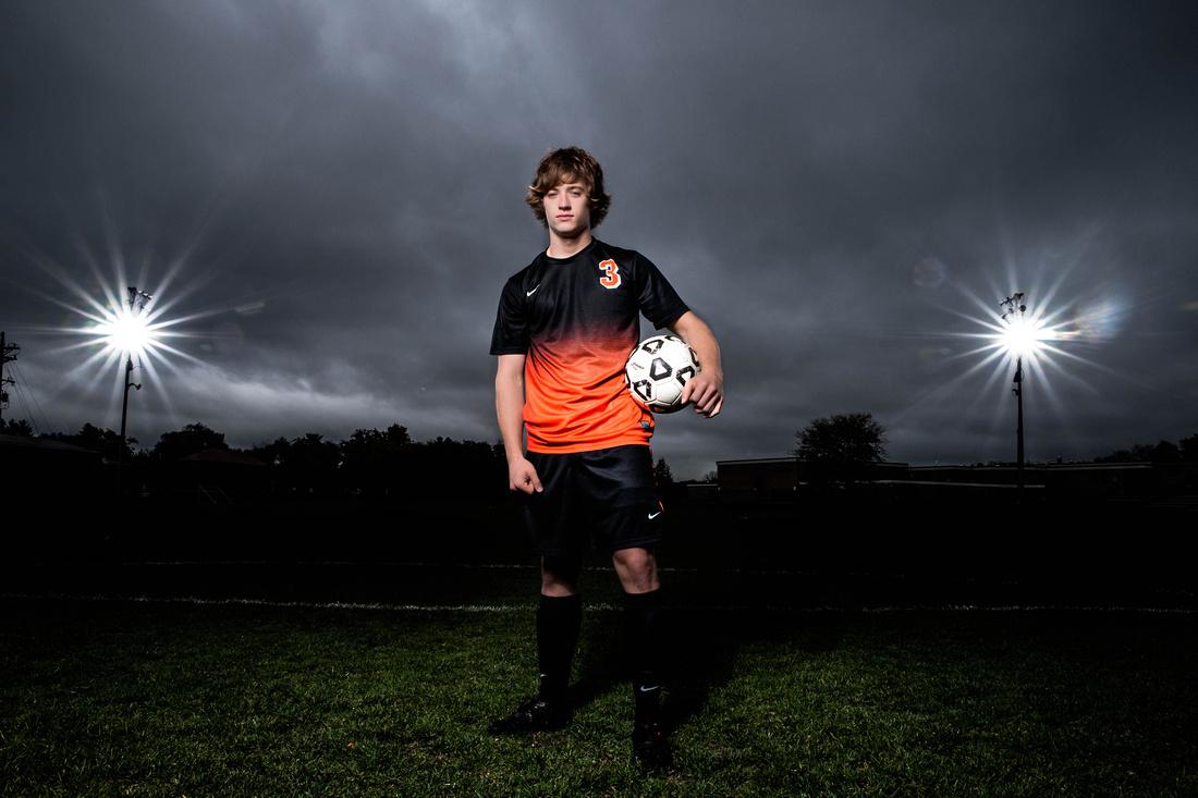 Senior Portrait Photography. senior standing on soccer field holding soccer ball.