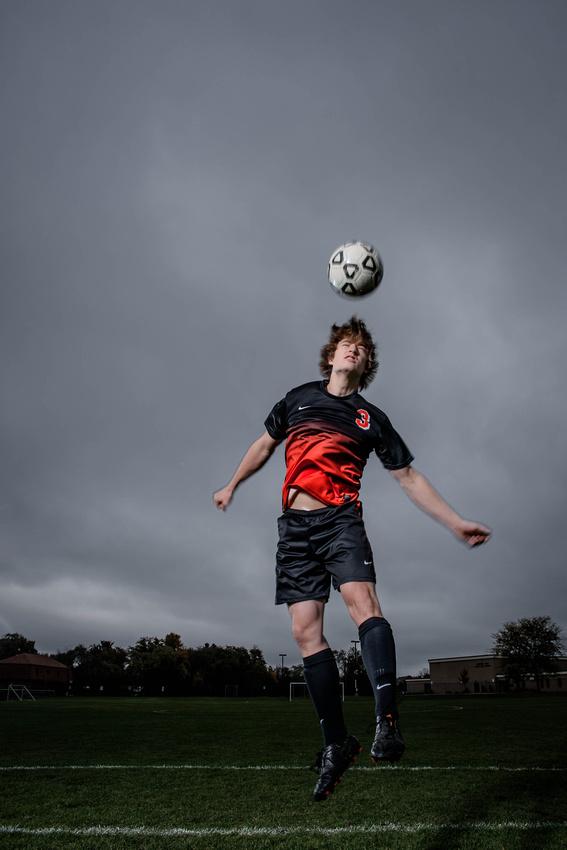Senior Portrait Photography. senior jumping in air to head a soccer ball